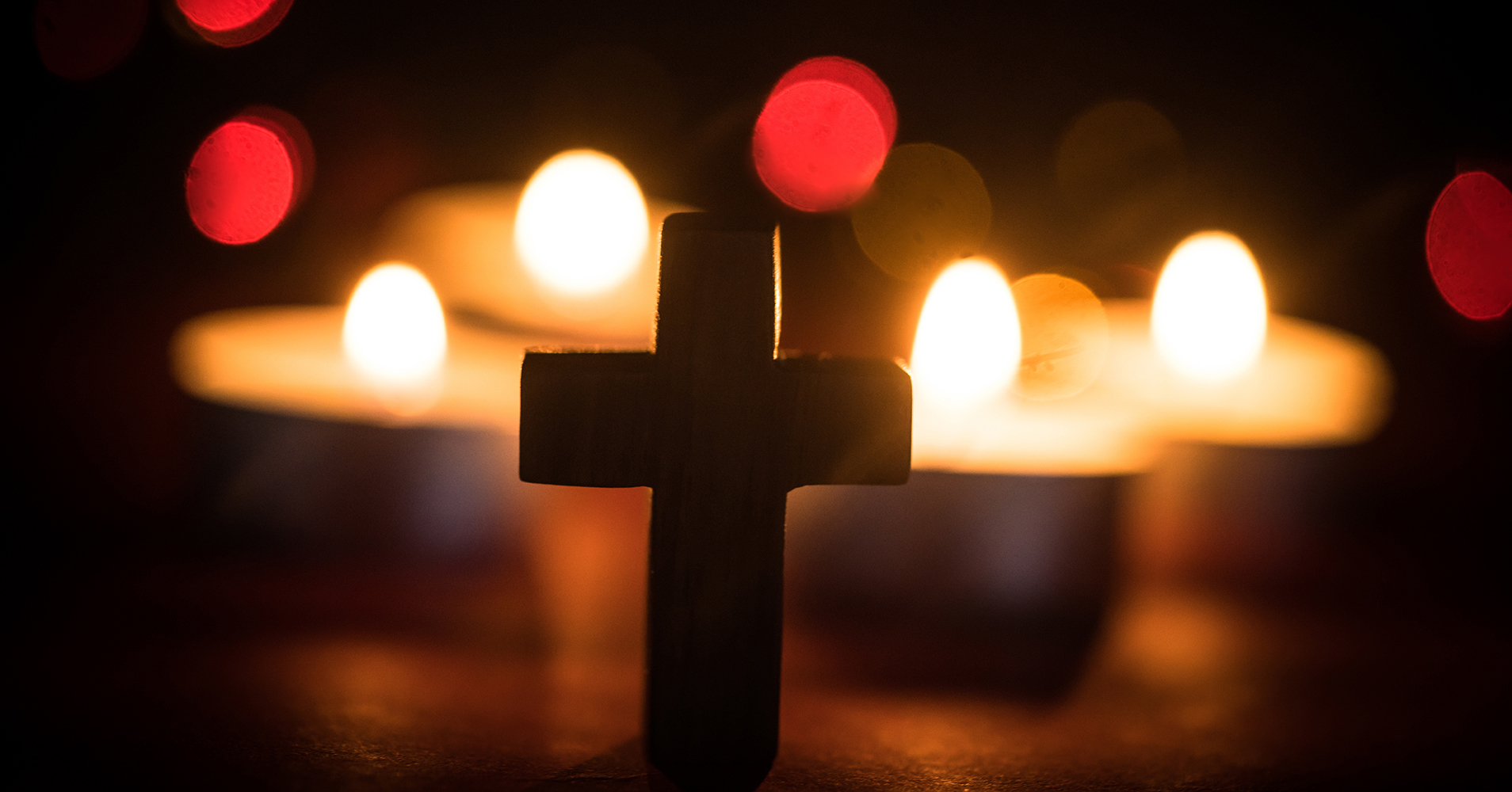 Stock image of tea-light candles behind a cross