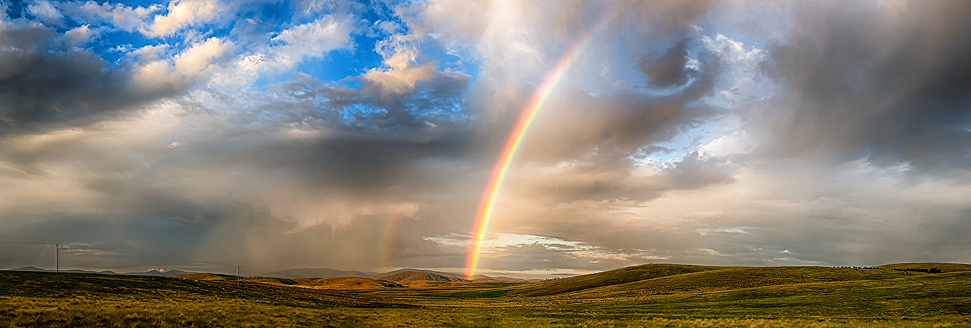 Stock image of rainbow against could sky on flat NSW landscape
